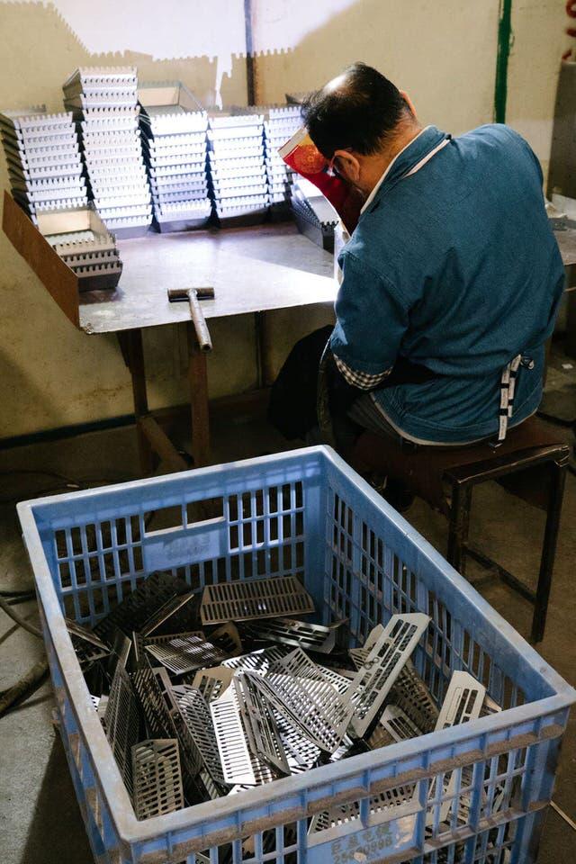 Bilde av arbeider i kina som lager pizzaovner for Gruue.